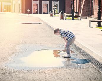 ילד מביט על שלולית מים -הילדים השקופים