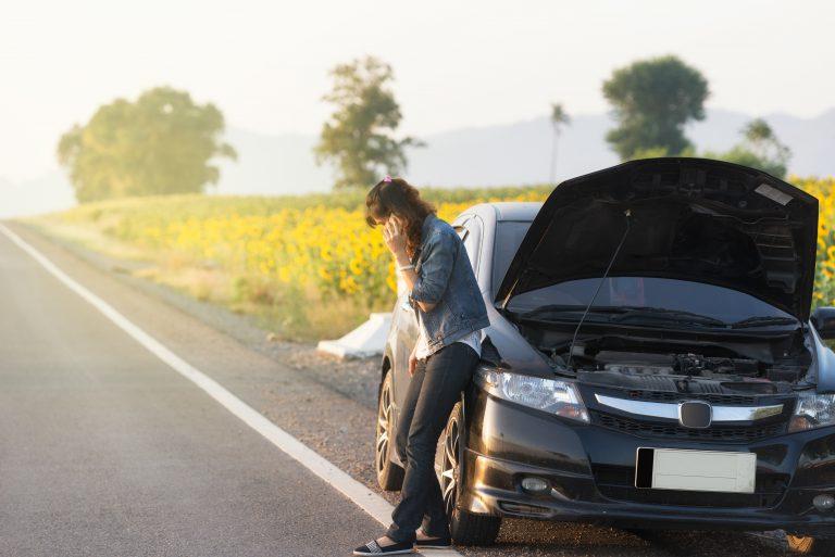 נערה שעונה על רכב תקוע מכסה מנוע פתוח