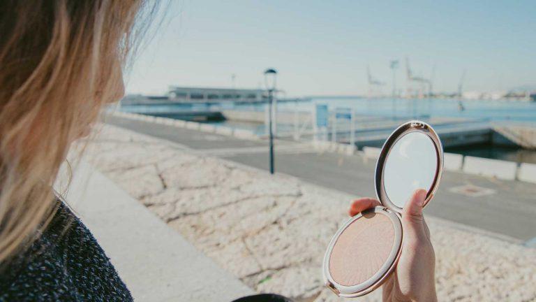 אישה מביטה במראת יד על חוף ים